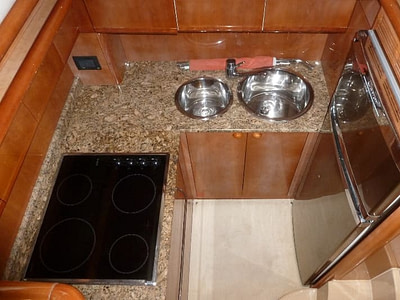 Kitchen with a stove, fridge and double sink onboard a Ferretti 480 yacht