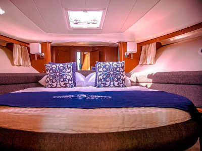 Luxurious cabin with a double bed, blue covers and designer pillows