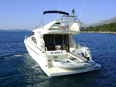 Ferretti 480 with a dinghy on the stern, at sea nearby an island