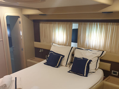 Double bed in a cabin with an ensuite bathroom onboard a Ferretti 591 yacht