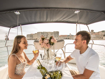 Couple enjoying wine on a sailing boat in front of the Old Town of Dubrovnik