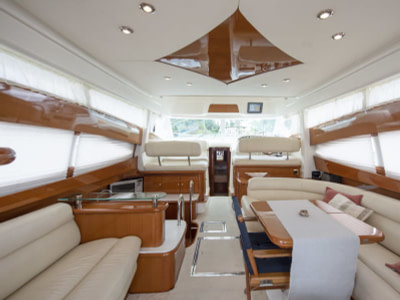 Indoor saloon with leather couches and wooden details inside a Prestige luxury yacht