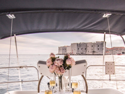 Romantic table setup with champagne and flowers on the main deck of a Sun Odyssey 32 in front of the Old Town of Dubrovnik
