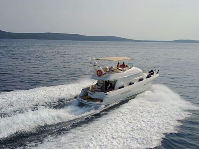 Aerial back view of a Motor yacht with guests cruising the Adriatic sea