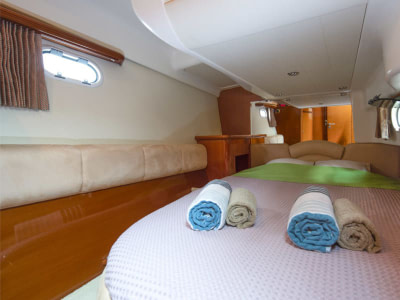 Double bed with linen and towels in a boat guest cabin