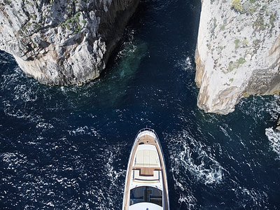 Aerial view of front of yacht docked between two large cliffs