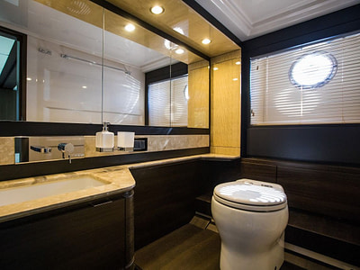 Ensuite bathroom with toilet and large mirrors onboard a yacht