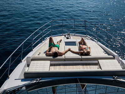 Couple sun tanning and holding hands on a yacht day tour