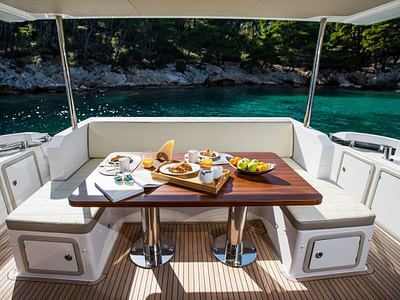 Breakfast served on a yacht table docked in front of an island