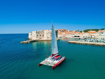 Large capacity red catamaran with open sails floating in front of Dubrovnik city walls, waiting for MICE tour to begin.