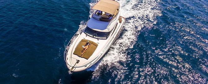Bird's eye view of a Prestige 440 cruising the Adriatic sea with a woman sunbathing on the sun deck