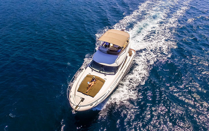 Bird's eye view of a Prestige 440 cruising the Adriatic sea with a woman sunbathing on the sun deck
